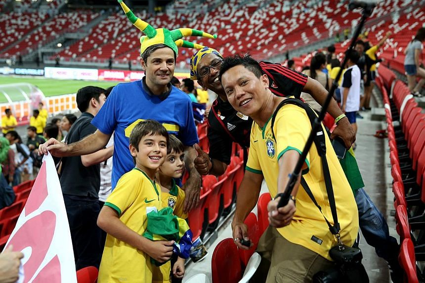 Fans taking a picture of themselves with a selfie stick after a friendly soccer match between Japan and Brazil at the National Stadium in October. Visitors are now not allowed to use the gadget inside the stadium, according to the Singapore Sports Hu