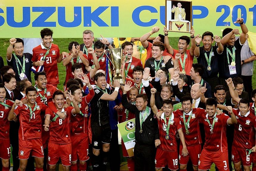 Thailand football team players celebrate with the trophy after defeating Malaysia 4-3 on aggregate during their AFF Suzuki Cup 2014 second-leg Final football match at the Bukit Jalil Stadium in Kuala Lumpur on Dec 20, 2014. -- PHOTO: AFP