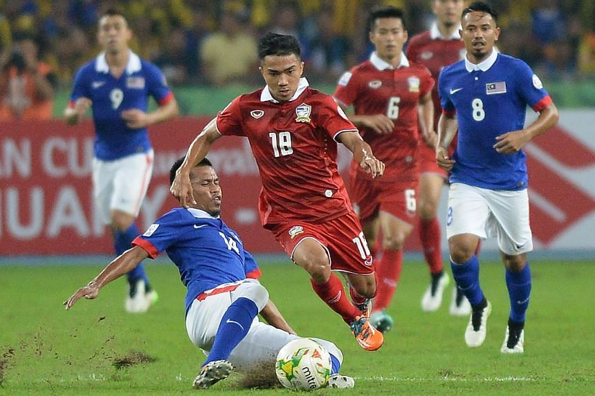 Thailand's Chanathip Songkrasin (middle) controls the ball against Malaysia's Badhri Radzi (bottom) during their AFF Suzuki Cup 2014 second-leg final football match at the Bukit Jalil National Stadium in Kuala Lumpur on Dec 20, 2014. -- PHOTO: A