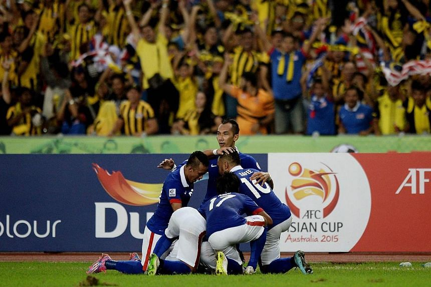 Malaysia's football team players celebrate their second goal against Thailand during their AFF Suzuki Cup 2014 second-leg Final football match at the Bukit Jalil Stadium in Kuala Lumpur on Dec 20, 2014.-- PHOTO: AFP
