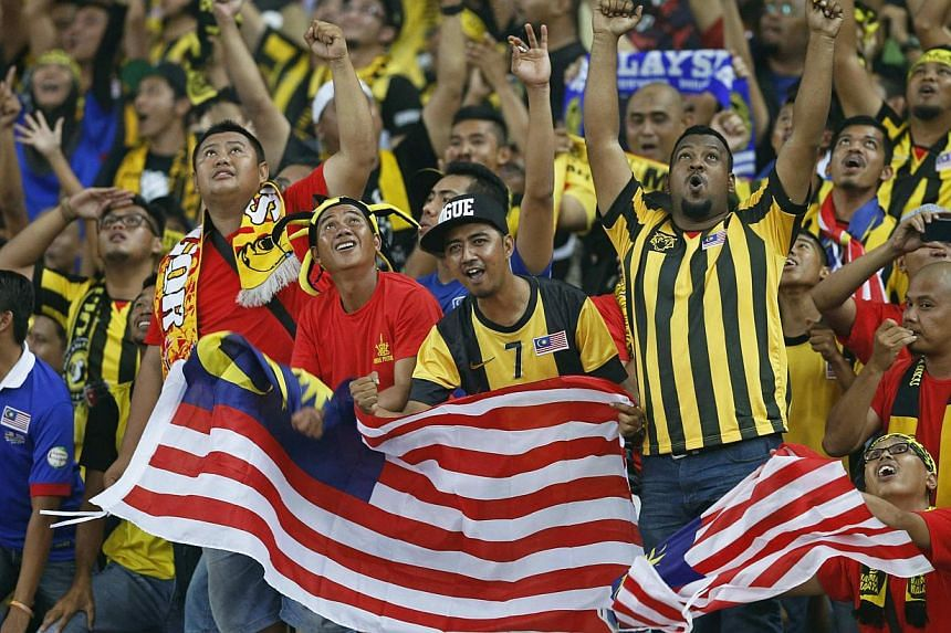 Fans of Malaysia cheer after the team scores the third goal during their Suzuki Cup final soccer match against Thailand at Bukit Jalil stadium in Kuala Lumpur on Dec 20, 2014.-- PHOTO: AFP