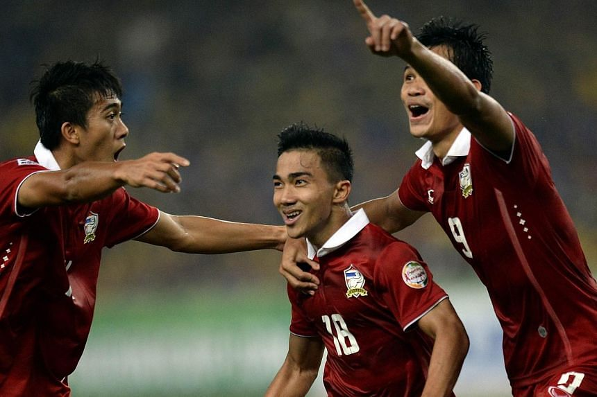 Thailand's Chanathip Songkrasin (middle) celebrates after scoring a goal against Malaysia during their AFF Suzuki Cup 2014 second-leg Final football match at the Bukit Jalil Stadium in Kuala Lumpur on Dec 20, 2014.-- PHOTO: AFP