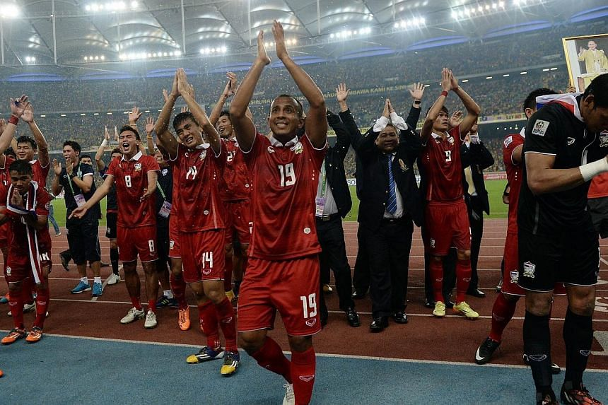 Thailand football team players celebrate after defeating Malaysia 4-3 on aggregate during their AFF Suzuki Cup 2014 second-leg Final football match at the Bukit Jalil Stadium in Kuala Lumpur on Dec 20, 2014. -- PHOTO: AFP