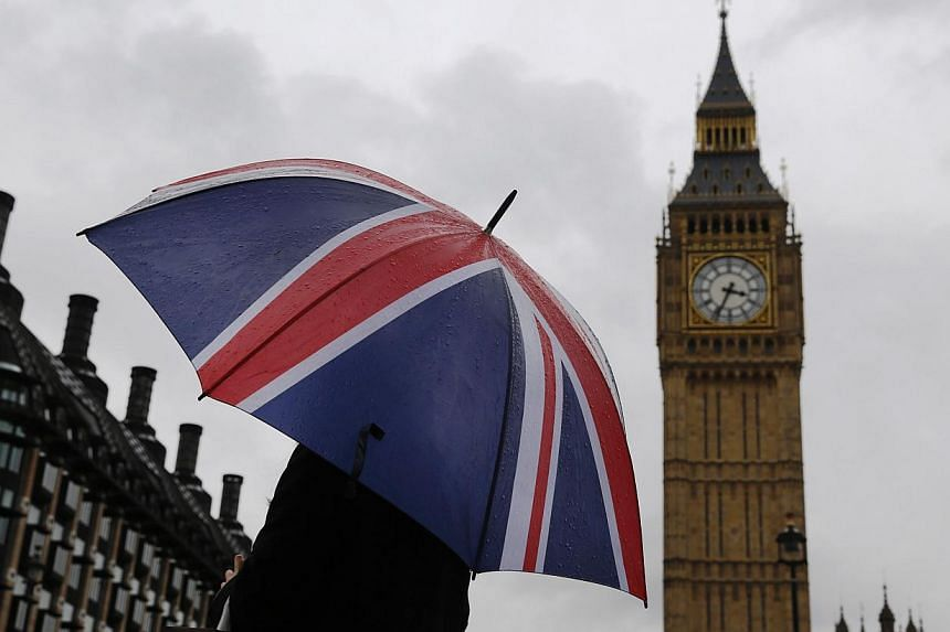 A person holds a Union flag umbrella in front of the Big Ben clock tower and Houses of Parliament in London, Britain, on Oct 4, 2014. A Singaporean who sees himself as a woman has failed in his bid to remain in the country on human rights grounds. --