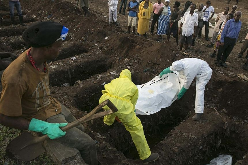 A grave digger watches as health workers carry the body of an Ebola victim for burial at a cemetery in Freetown on Dec 17, 2014. -- PHOTO: REUTERS