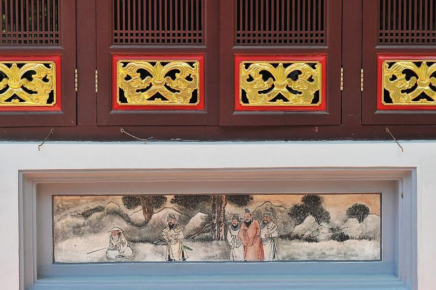 Timber windows (top) and fresco wall painting at the Keng Teck Building in the temple.-- PHOTO: LIM YAOHUI FOR THE STRAITS TIMES
