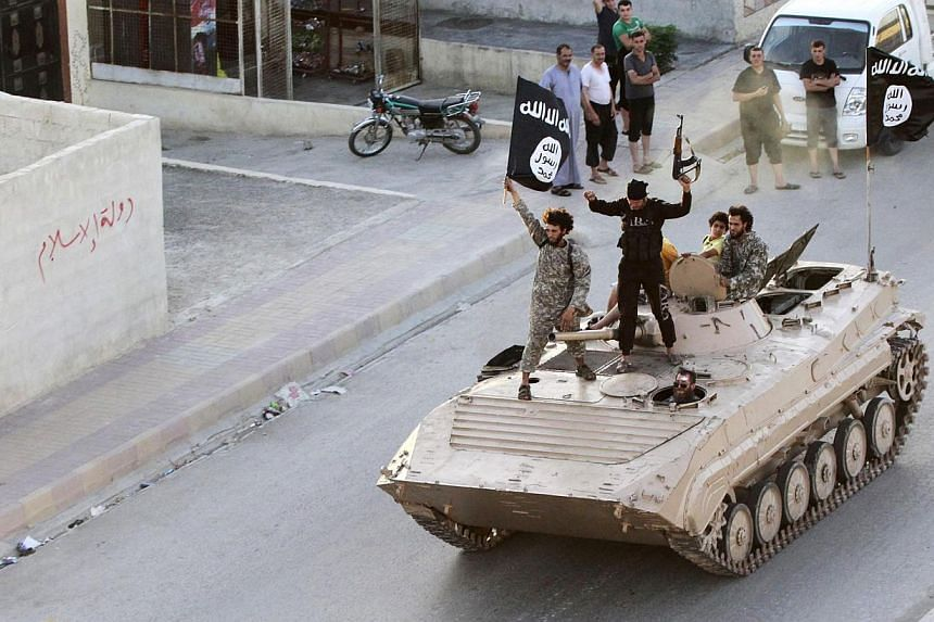 Men hold the flag of Islamic State in Iraq and Syria (ISIS) while taking part in a military parade along the streets of northern Raqqa province on June 30, 2014. -- PHOTO: REUTERS