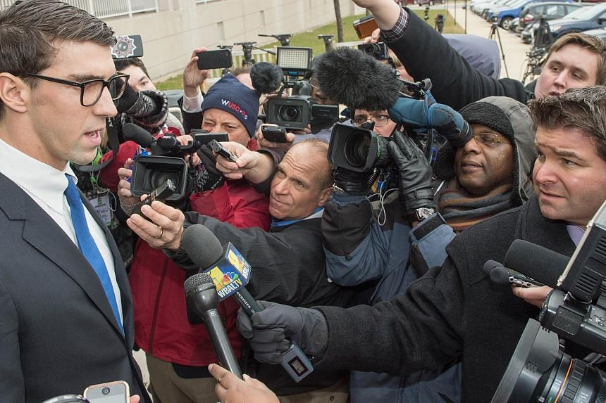 Olympic swimming champion Michael Phelps (left) speaks to the press after his trial on Dec 19, 2014 in Baltimore, Maryland. Phelps was given a one-year suspended sentence and 18 months probation after his arrest for driving under the influence of alc