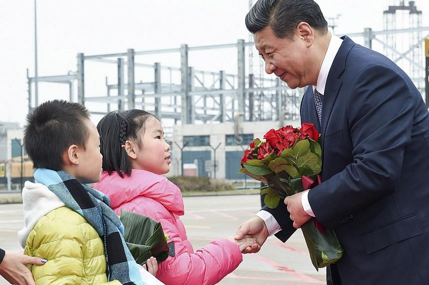 Chinese President Xi Jinping shakes hands with a child as he receives a bouquet upon arriving in Macau to celebrate the 15th anniversary of its handover to the mainland on Dec 19, 2014. -- PHOTO: REUTERS