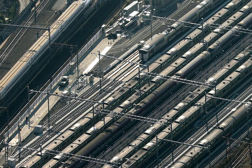 A Central Japan Railway Co. Shinkansen bullet train, left, travels near East Japan Railway Co. trains in this aerial photograph taken in Tokyo, Japan, on Monday, Dec. 2, 2013. Thailand is talking to Japan with a view to building three rail routes in