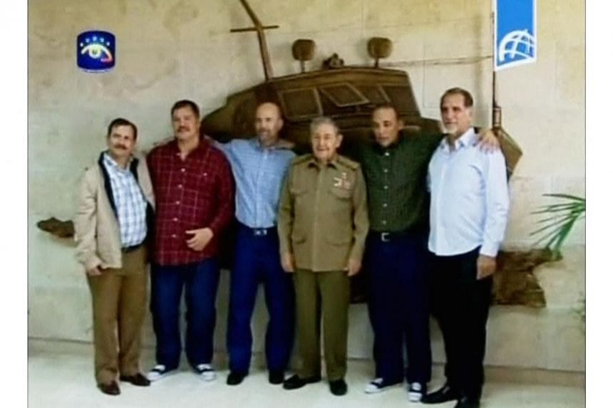 Cuban President Raul Castro (C) poses with three Cuban intelligence agents released by the U.S. government, after they returned to Havana on Wednesday, in this image taken from government television. The President seems to have scored a diplomatic tr