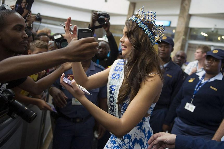 Rolene Strauss, the newly crowned Miss World 2014, signs autographs as she arrives at OR Tambo International Airport, in Johannesburg on Dec 20, 2014. -- PHOTO: AFP