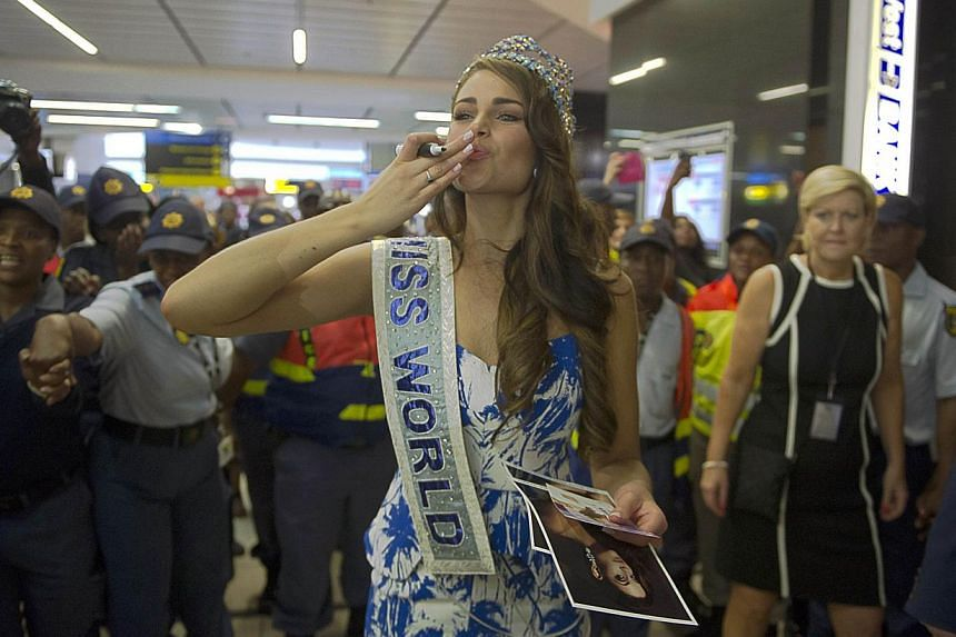 Rolene Strauss, the newly crowned Miss World 2014, blows a kiss as she arrives at OR Tambo International Airport, in Johannesburg on Dec 20, 2014. -- PHOTO: AFP