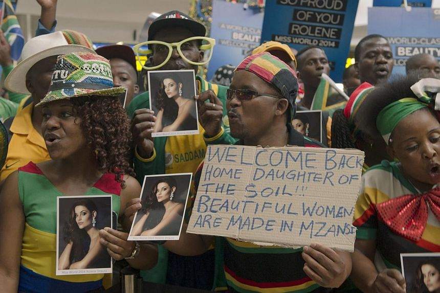 Fans wait to welcome Rolene Strauss (unseen), the newly crowned Miss World 2014, upon her arrival at OR Tambo International Airport, in Johannesburg on Dec 20, 2014. -- PHOTO: AFP