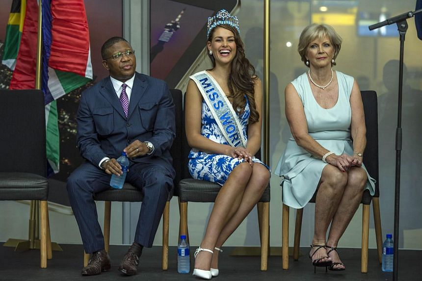(From left) South African Minister of Sport and Recreation Fikile Mbalula, Rolene Strauss, the newly crowned Miss World 2014, and South African 1958 Miss World, Penny Coelen Rey, attend a ceremony at OR Tambo International Airport, in Johannesburg on