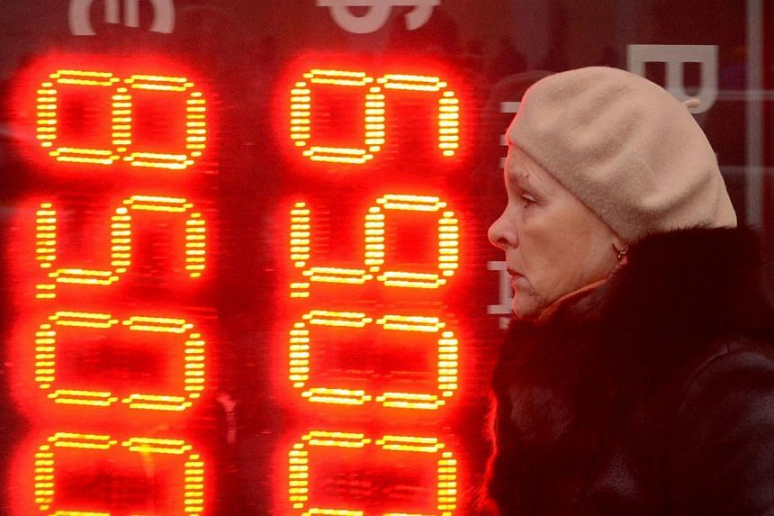 A woman walks past a board listing foreign currency rates against the Russian rouble outside an exchange office in central Moscow on Dec 16, 2014.Western companies are curtailing investments in Russia, repatriating funds and talking with