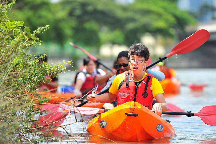 Mr Chan Yin King, 23, Undergraduate and Deaf participant from Singapore Association for the Deaf, picking up litter in the waterway along sungei geylang on Dec 20, 2014.-- PHOTO:LIM YAOHUI FOR THE STRAITS TIMES