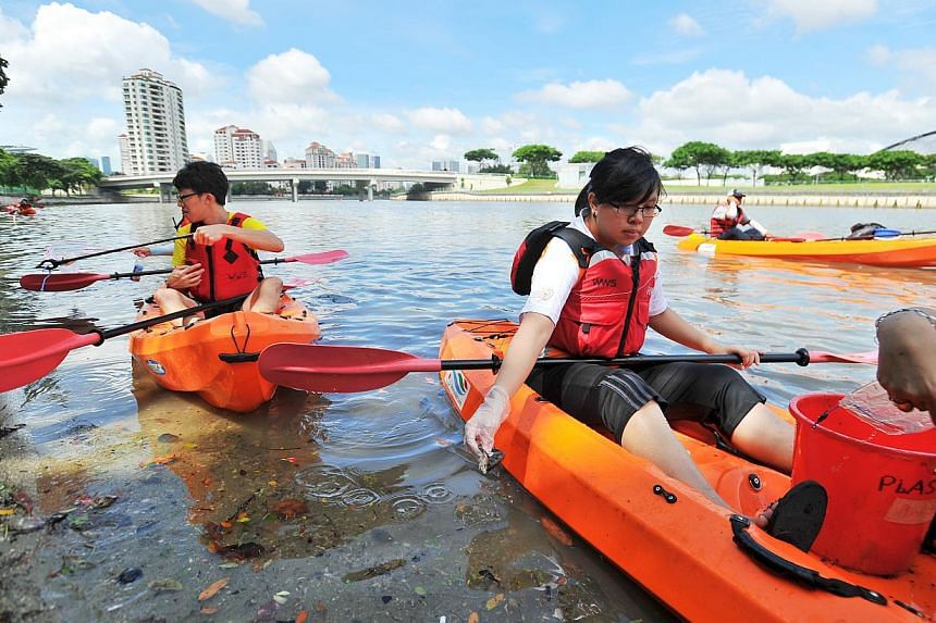 Ms Nancy Teoh (right), SADeaf YouthBeat volunteer, picking up litter in the waterway along sungei geylang on Dec 20, 2014.-- PHOTO:LIM YAOHUI FOR THE STRAITS TIMES