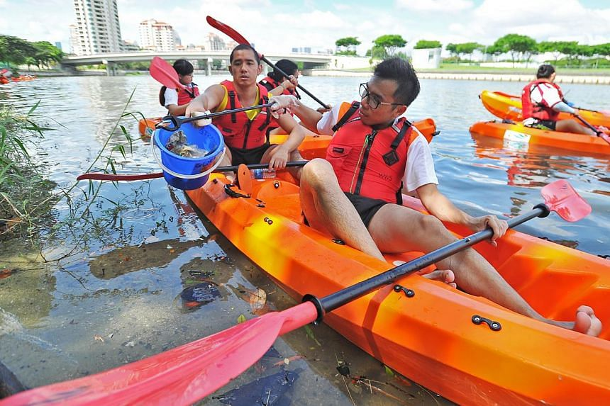 Mr Lim Jing Jie (right), 25, SADeaf YouthBeat volunteer, picking litter from the waterway along sungei geylang and throwing into the blue pail held by deaf participant Nicholas Eaw Cheng Shun, 29, 3D artist on Dec 20, 2014.-- PHOTO:LIM YA