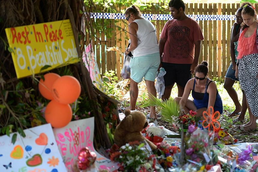 Mourners at the scene where eight children ranging from babies to teenagers were found dead in a house in the northern Australian city of Cairns. A 37-year-old woman, the mother of all but one of the eight children, has been charged with eight counts
