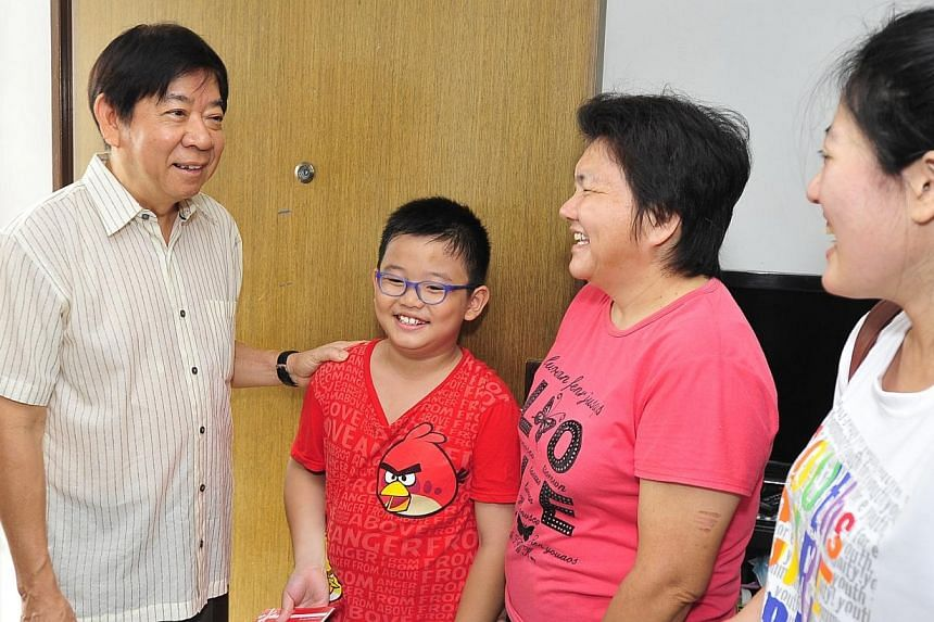 (From left) Minister for National Development Khaw Boon Wan, talking with backpack recipient, Ng Ah Jun, 7, his mother Ng Chiew Keok, 50, and Chairman of the Sembawang CC Youth Executive Committee Gillian Goh. -- PHOTO: DIOS VINCOY JR FOR T