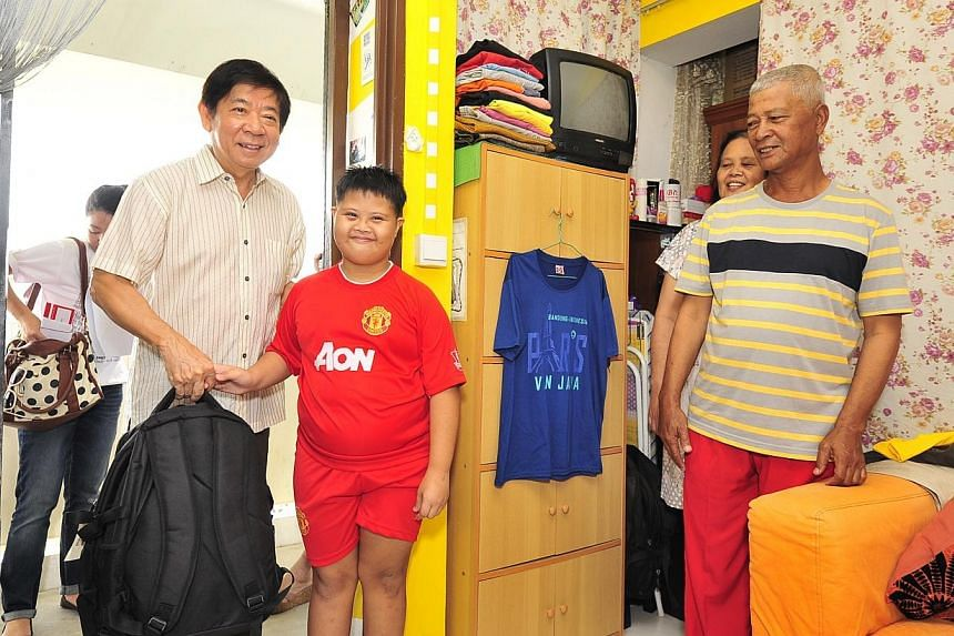 Minister for National Development Khaw Boon Wan, handing over a backpack to Muhd Hykel,12, while his parents,  Madam Mahani bin Samat, 54 and Mr Rolsi bin Baba, 54, look on. -- PHOTO: DIOS VINCOY JR FOR THE STRAITS TIMES