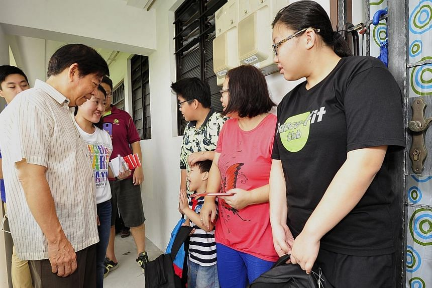 (From left) Minister for National Development Khaw Boon Wan and Ms Gillian Goh, chairman of the Sembawang CC Youth Executive Committee, speaking with Kelvan Teo, 13, Kelson Teo, 5, Madam Jennifer Tan, 47 and Jasyln Teo, 15.-- PHOTO:DIOS V