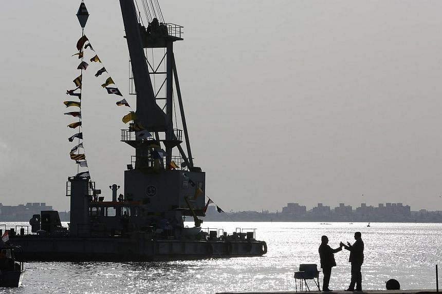 People talk as they stand looking over the Suez Canal in Ismailia city on Nov 13, 2014.An Egyptian court has jailed a Suez Canal shipping services manager for 10 years on charges of spying for Israel about naval movements through the strategic