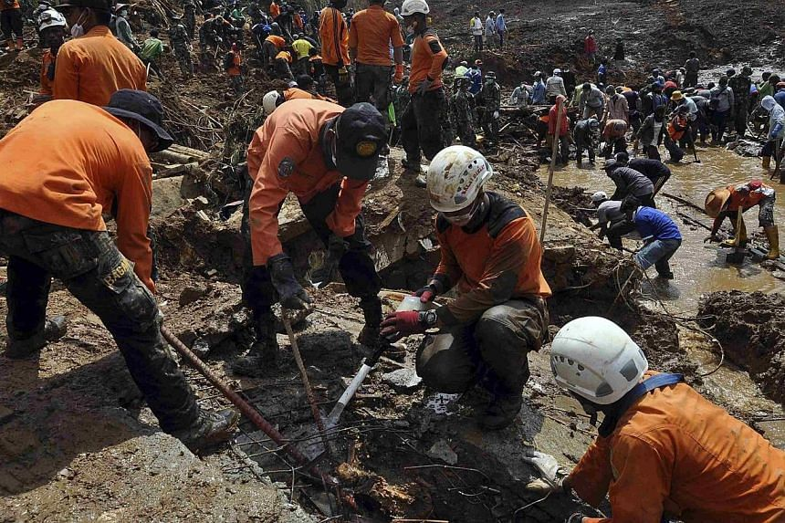 Rescue team members and soldiers use shovels during the search for landslide victims who are still buried in Sampang village in Banjarnegara, in this Dec 16, 2014 photo taken by Antara Foto.Indonesian rescuers on Sunday, Dec 21, ended their sea