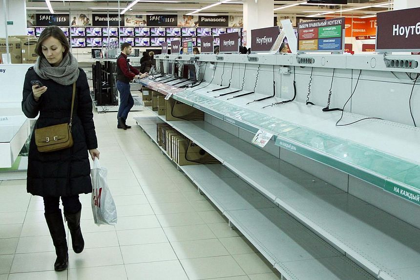 A woman walks past the empty shelves in an electronic shop in Minsk, on Dec 21, 2014.Belarus blocked online stores and news websites on Sunday, Dec 21, 2014, in an apparent attempt to stop a run on banks and shops as people rushed to secure the