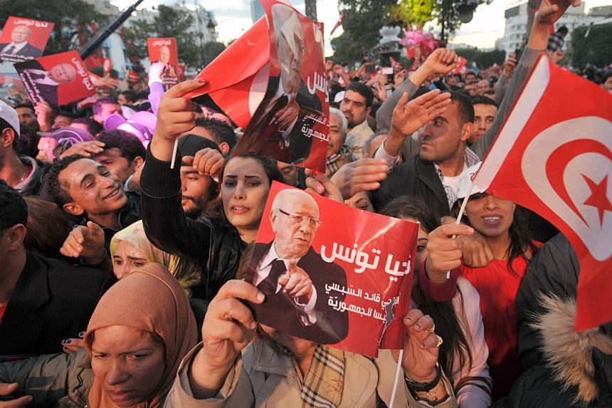 Supporters of Tunisian presidential candidate Beji Caid Essebsi attend his last meeting on Dec 19, 2014, on the Avenue Bourguiba in Tunis.Tunisians voted on Sunday, Dec 21, in the runoff of the first free presidential election in the North Afri