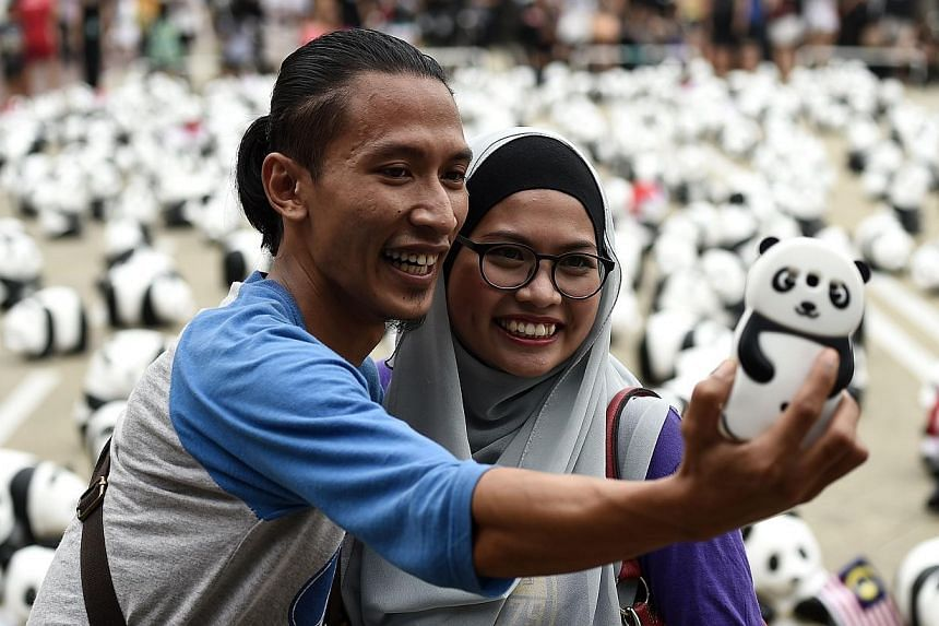 A Malaysian couple takes a selfie as they pose with some of the 1,600 papier-mache pandas displayed at Independence Square in Kuala Lumpur on Dec 21, 2014, as part of their first appearance in the city. -- PHOTO: AFP