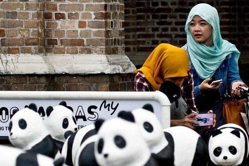 Malaysian women pose with some of the 1,600 papier-mache pandas displayed at Independence Square in Kuala Lumpur on Dec 21, 2014, as part of their first appearance in the city. -- PHOTO: AFP