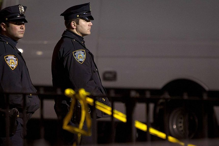 Police are pictured at the scene of a shooting where two New York Police officers were shot dead in the Brooklyn borough of New York on Dec 20, 2014. -- PHOTO: REUTERS