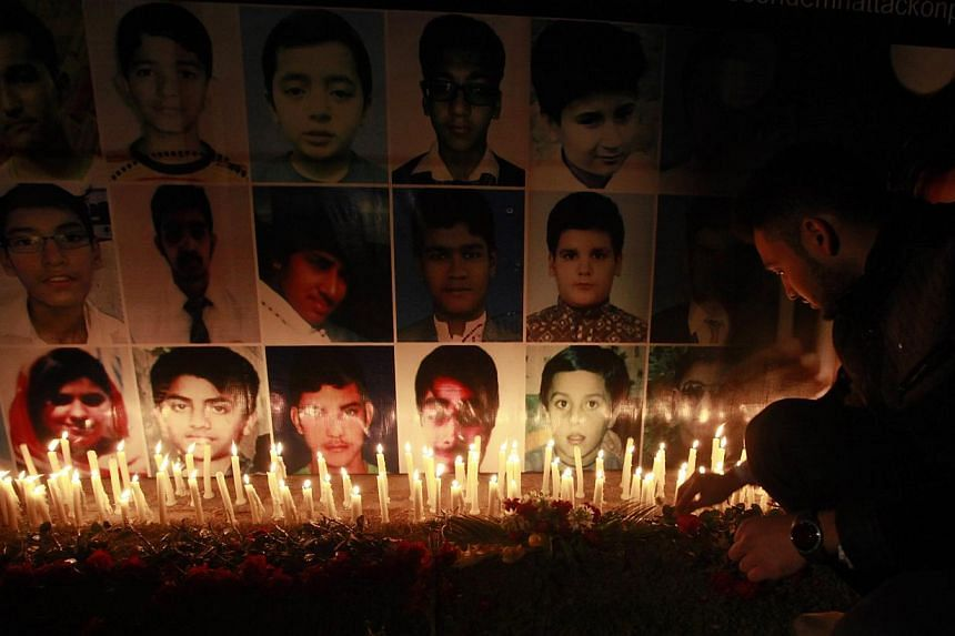 A man places a rose after lighting candles in front of portraits of the victims of the Taleban attack on the Army Public School in Peshawar, during a candlelight vigil in Lahore on Dec 19, 2014.Al-Qaeda's regional branch on Sunday, Dec 21, said