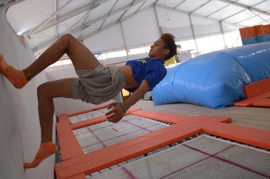 """A visitor """"climbs"""" the wall (above), using momentum gained from the trampoline mats, while others play dodgeball. --ST PHOTO: MARK CHEONG"""