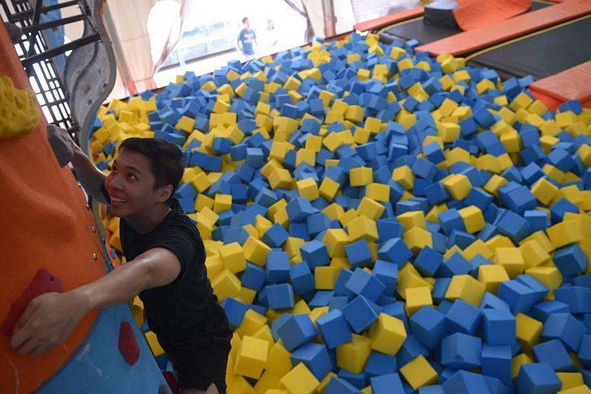 Reporter Benson Ang jumping onto the 11m-long airbag, which is accessible via five lanes and climbing (above) the 3.5m-high rock wall at Zoom Park Singapore, from which climbers can fall safely into the foam pit below.--ST PHOTO: MARK CHE