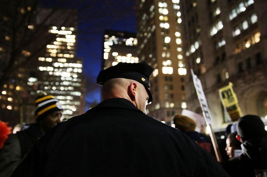A police officer stands guard as people demonstrate outside City Hall against police violence at a rally that was supposed to be in support of the New York Police Department on Dec 19, 2014 in New York City. Two New York police officers were sho