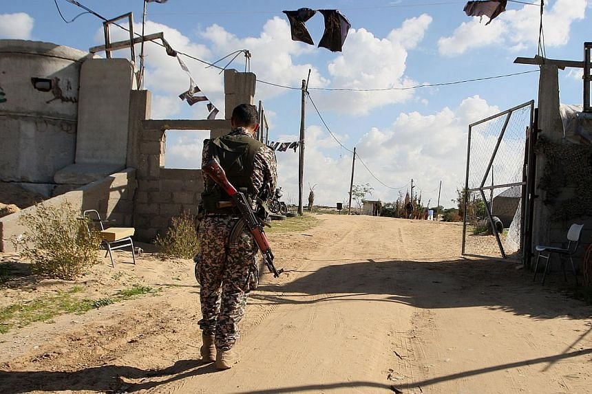 A Palestinian militant from the Islamic Jihad armed wing, the Al-Quds Brigades, walks near a military post on Dec 20, 2014 in Khan Yunis, in the southern Gaza Strip. Israeli jets struck targets in the southern Gaza Strip, witnesses and the army said