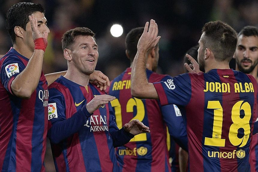 Barcelona's Argentinian forward Lionel Messi (second left) is congratulated by his teammates after scoring during the Spanish league football match FC Barcelona versus Cordoba CF at the Camp Nou stadium in Barcelona on Dec 20, 2014. Barcelona won 5-0