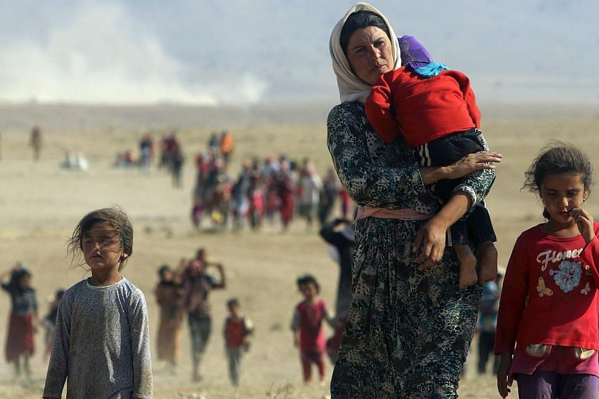 Displaced people from the minority Yazidi sect, fleeing violence from forces loyal to the Islamic State in Sinjar town, walk towards the Syrian border on Aug 11, 2014. Iraqi Kurdish leader Massud Barzani hailed victories over the Islamic State i