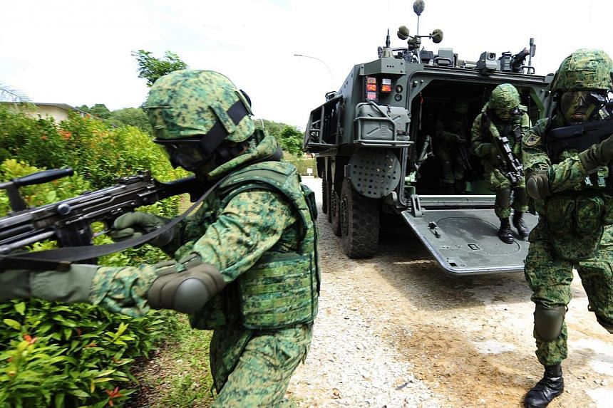 Soldiers exiting the Singapore Armed Forces' (SAF) Terrex Infantry Carrier Vehicle (ICV), an armoured infantry carrier. The Ministry of Defence is looking for civilian companies to take over the task of washing armoured vehicles and more. -- PHOTO: S