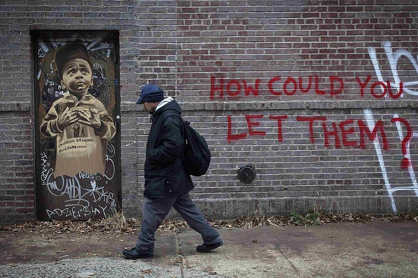 A man walks past some fresh graffiti very near the site where two police officers were shot in the head in the Brooklyn borough of New York on Dec 21, 2014. -- PHOTO: REUTERS
