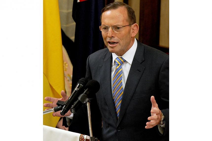 In opposition, Mr Abbott claimed repealing the carbon tax would help women, because it would lower electricity costs associated with ironing. -- PHOTO: AFP