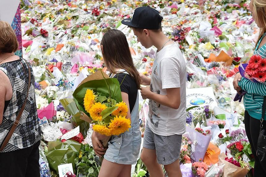 Visitors carry flowers to lay at a makeshift memorial near the scene of the fatal siege in the heart of Sydney's financial district, on Dec 18, 2014. Amirah Droudis, the partner of a self-styled Sheikh who last week stormed the cafe at gunpoint, has