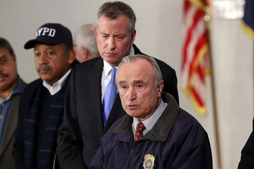 New York City Police Commissioner William J. Bratton is joined by Mayor Bill de Blasio at a news conference at Woodhull Hospital following the killing of two New York City police officers on Dec 20, 2014 in New York City. -- PHOTO: AFP