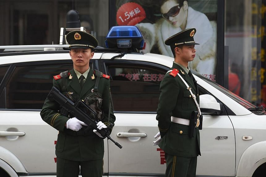 Chinese paramilitary police officers watch over pedestrians in the Wangfujing shopping district in Beijing on Oct 24, 2014. The mother of a man executed 20 years ago for a murder to which another person later confessed appeared in a Chinese cour