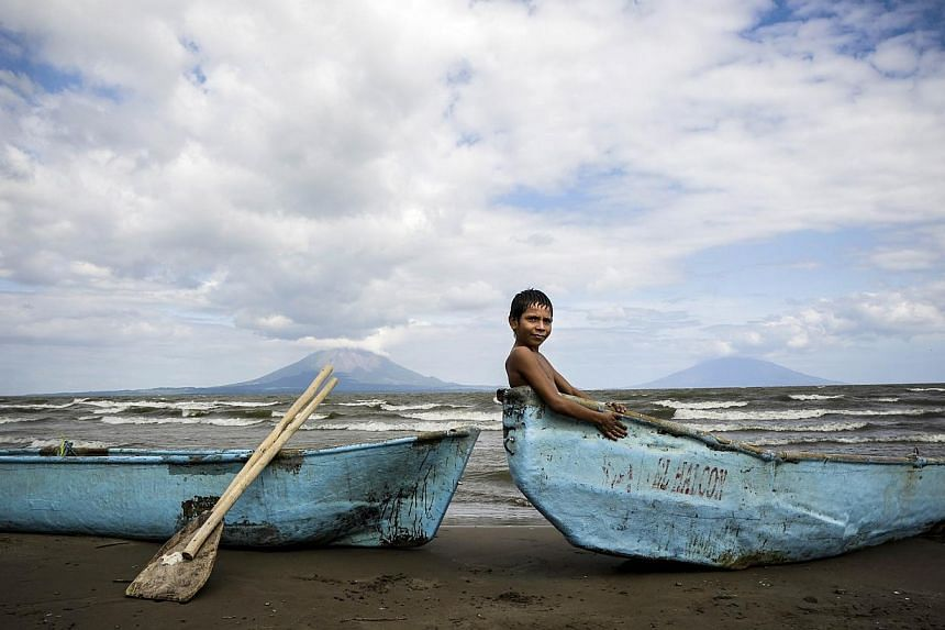 A boy is seen sitting in a boat along the shore of Cocibolca lake in Rivas, Nicaragua on Dec 11, 2014. The construction of Nicaragua's controversial US$50-billion (S$62.52 billion) canal linking the Pacific Ocean and the Caribbean begins Monday,