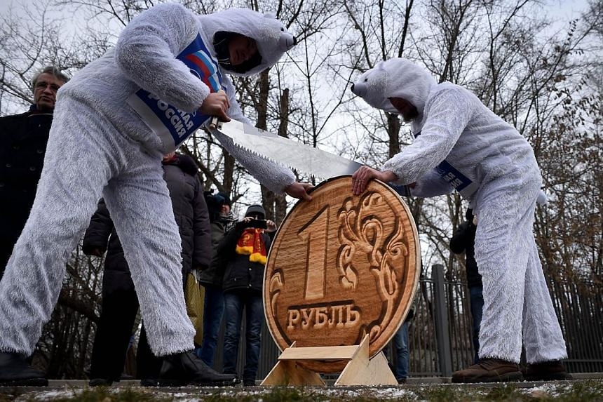Russia's Communist Party supporters dressed as white bears, symbol of pro-President party United Russia, saw a model of a one Russian ruble coin during a rally against ruble fall in exchange in front of the headquarters of the government in central M