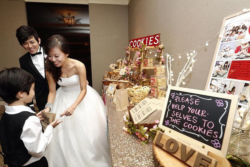 Ms Sue-Ann Phay, in her early 30s, and Mr Boaz Chan, 30, giving out cookies at their wedding reception last Saturday. The counter had a write-up and photos explaining that the cookies were baked by clients from the Movement for the Intellectually Dis